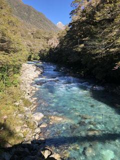 山の中腹に木と岩の多い川の写真・画像素材[1250335]