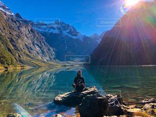 水の横にある岩の上に座っている女の写真・画像素材[1250341]