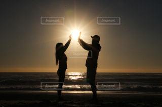 日没の太陽を持っているカップルの写真・画像素材[1377381]