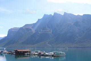 背景の山と水の体中の小型船の写真・画像素材[1532442]