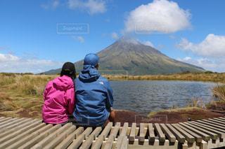 大きな山の前に座っているカップルの写真・画像素材[1532483]