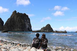 ビーチの前で座っているカップルの写真・画像素材[1552574]