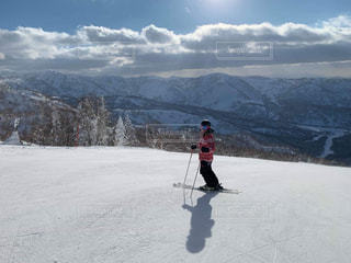 雪に覆われた斜面をスキーに乗っている男の写真・画像素材[2098238]