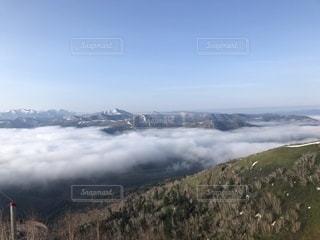 雪に覆われた山の上空の雲のグループの写真・画像素材[2140338]