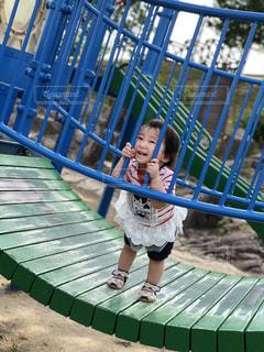 金属フェンスの背に乗る少女の写真・画像素材[1207740]