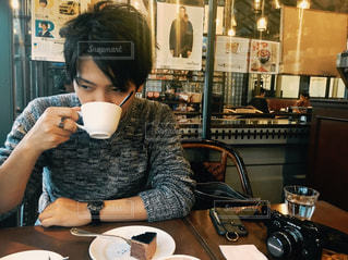 テーブルに座っている男性の写真・画像素材[1211256]
