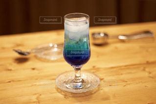 木製テーブルの上に座っているグラスワインの写真・画像素材[1226593]
