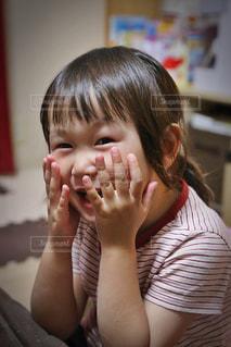 テーブルに座って笑っている少女の写真・画像素材[1215945]