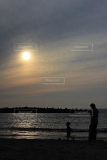 夕焼けバックにビーチで遊ぶ親子の写真・画像素材[1266172]