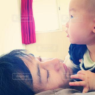 昼寝中の父の上に乗る赤ちゃんの写真・画像素材[1266174]