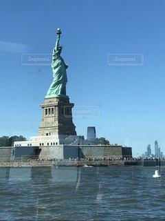 水の体の上にそびえ立つ大きな時計塔の写真・画像素材[1294927]