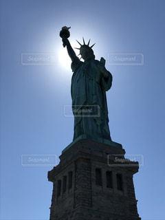 天使の丘とバック グラウンドで像の隣に座って背の高い時計塔の写真・画像素材[1294934]