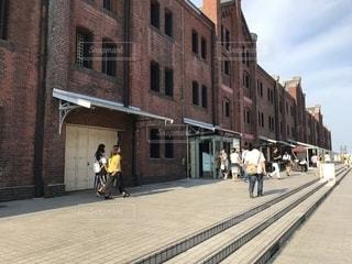 れんが造りの建物の横にある道を歩いて人々 のグループの写真・画像素材[1425956]