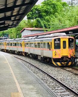 駅の近くを線路を下る黄色い列車の写真・画像素材[2265121]