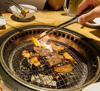 ストーブで食べ物を調理する人の写真・画像素材[2418359]