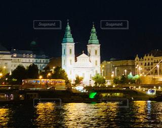 水域の前で夜にライトアップされた都市の写真・画像素材[2697960]