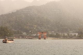 背景の山と水の体のボートの写真・画像素材[1222786]