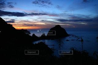 背景の山が付いている水の体に沈む夕日の写真・画像素材[1429721]