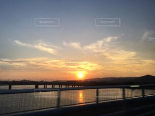 背景の夕日と水の体の上の橋の写真・画像素材[1226547]