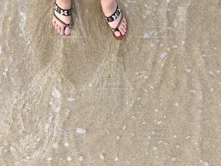 砂浜で波に足を浸しての写真・画像素材[1226557]