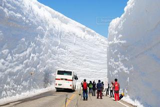雪に覆われた山の頂上に立っている人々 のグループの写真・画像素材[1226312]