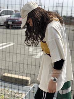 フェンスの前に立っている女性の写真・画像素材[1225576]