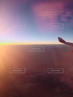 バック グラウンドで夕日を持つ人の写真・画像素材[1233388]