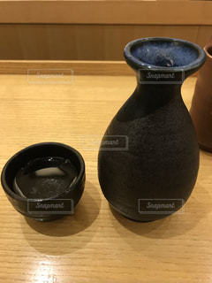 木製テーブルの上に座っている花瓶の写真・画像素材[1249587]