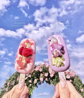 バラ園でアイスクリームを持っている手 - No.1227800