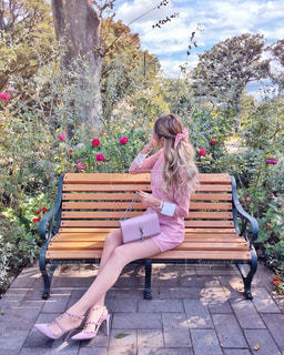 木製のベンチに座っている人の写真・画像素材[1228043]