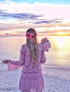 海に浮かぶ夕日を眺める女性の写真・画像素材[1229153]