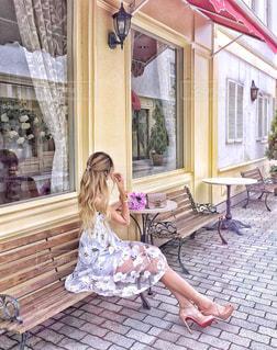建物の前にあるベンチに座っている女の子の写真・画像素材[1268612]