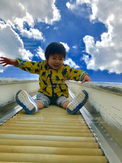 滑り台を滑っている少年の写真・画像素材[1229495]