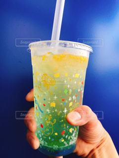 プラスチック製のカップを持っている手の写真・画像素材[1230307]