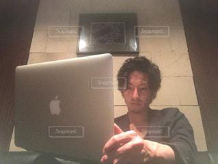 ノート パソコンの前に座っている男の写真・画像素材[1233606]