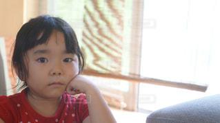 窓の前に座っている少女の写真・画像素材[1258265]