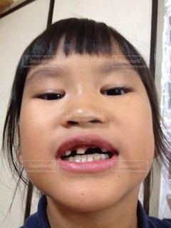 近くにカメラに向かって笑みを浮かべて少女のアップの写真・画像素材[1231476]