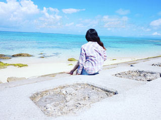 水の体の近くのビーチに座っている人の写真・画像素材[1816279]