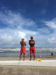 夏の海に立つ2人コンビのライフセーバーの写真・画像素材[1557647]