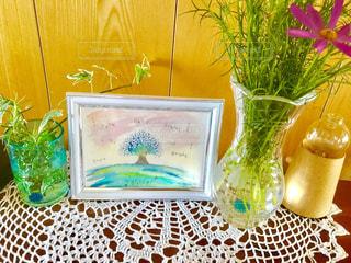 テーブルの上の絵と花の写真・画像素材[1383600]