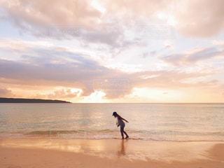 夕暮れのビーチを歩く女性の写真・画像素材[1245021]