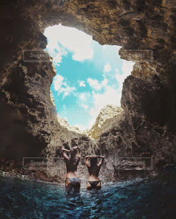 背景の山と水の中を泳いでいる人の写真・画像素材[1245024]