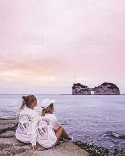 海で夕暮れを眺める女性の写真・画像素材[1245064]
