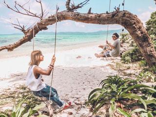 ビーチでヤシの木の横に立っている人の写真・画像素材[1245107]