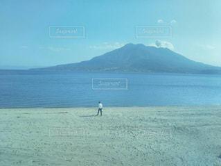 桜島を斜めに海へ向かう男の写真・画像素材[1713231]