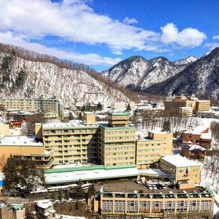 雪に覆われた山と温泉宿の写真・画像素材[1249858]