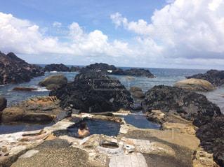 水の体の横にある岩のビーチの写真・画像素材[1250948]