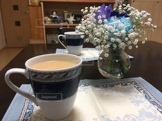 紅茶とテーブルの上の花の花瓶の写真・画像素材[1291852]