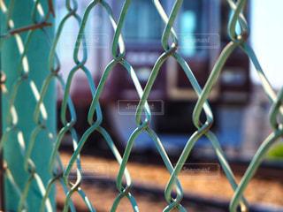 フェンス越しの電車の写真・画像素材[2053581]