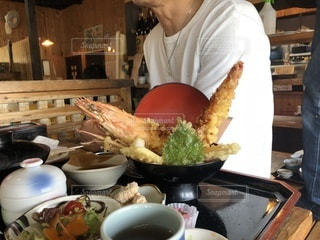 食品のプレートをテーブルに着席した人の写真・画像素材[1258932]